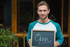 Portrait of smiling waiter holding chalkboard with open sign Stock Image