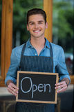 Portrait of smiling waiter showing chalkboard with open sign Stock Images