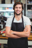 Portrait of smiling waiter standing with arm crossed. In cafe Stock Image