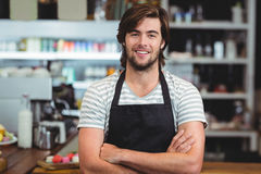 Portrait of smiling waiter standing with arm crossed. In cafe Stock Photography