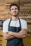 Portrait of smiling waiter standing with arms crossed. In caf Stock Image