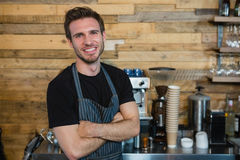 Portrait of smiling waiter standing with arms crossed. In caf Stock Photos