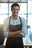 Portrait of smiling waiter standing with arms crossed. In cafe Stock Photography