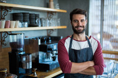 Portrait of smiling waiter standing with arms crossed. In cafe Royalty Free Stock Photo