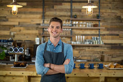 Portrait of smiling waiter standing with arms crossed. In cafe Royalty Free Stock Photos