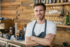 Portrait of smiling waiter standing with arms crossed at counter. In caf Royalty Free Stock Photo