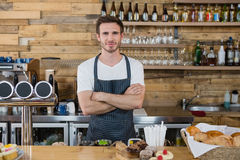Portrait of smiling waiter standing with arms crossed at counter. In cafe Stock Photo