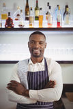 Portrait of smiling waiter standing with arms crossed at counter. In restaurant Stock Images