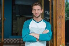 Portrait of smiling waiter standing with arms crossed. At entrance of cafe Stock Images