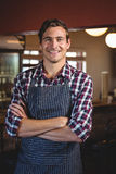 Portrait of smiling waiter standing with arms crossed. In restaurant Royalty Free Stock Photo