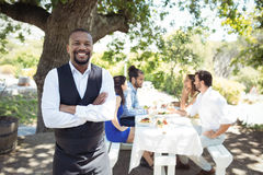 Portrait of smiling waiter standing with arms crossed. In restaurant Stock Images