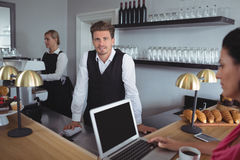 Portrait of smiling waiter standing at bar counter. In restaurant Royalty Free Stock Photo