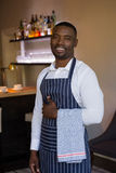 Portrait of smiling waiter standing with towel. In restaurant Stock Images