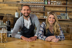 Portrait of smiling waiter and waitress leaning at counter stock photo