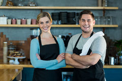 Portrait of smiling waiter and waitress standing with arms crossed. In cafe Stock Image