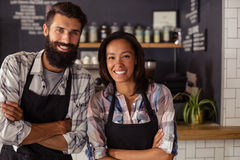 Portrait of smiling waiter and waitress standing with arms crossed. In cafe Royalty Free Stock Images