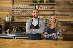 Portrait of smiling waiter and waitress standing with arms crossed at counter. In caf Royalty Free Stock Image