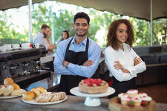 Portrait of smiling waiter and waitress standing with arms crossed at counter. In restaurant Stock Photography