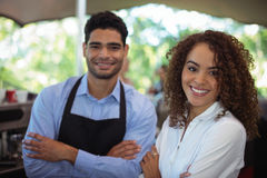 Portrait of smiling waiter and waitress standing with arms crossed at counter. In restaurant Stock Photos