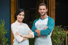 Portrait of smiling waiter and waitress standing with arms crossed. Outside the cafe Stock Photos