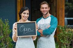Portrait of smiling waiter and waitress standing with chalkboard. Outside the cafe Royalty Free Stock Photos