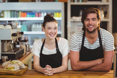 Portrait of smiling waiter and waitress standing at counter. In cafe Royalty Free Stock Photography