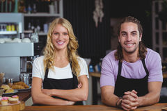 Portrait of smiling waiter and waitress standing at counter. In cafe Stock Images