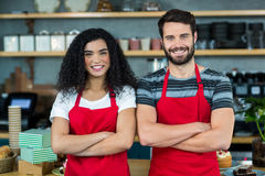 Portrait of smiling waiter and waitress standing at counter. In cafe Royalty Free Stock Images