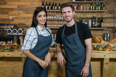 Portrait of smiling waiter and waitresses standing at counter Royalty Free Stock Photography