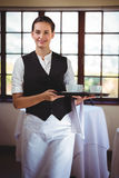 Portrait of smiling waitress holding a tray of coffee cups Stock Image