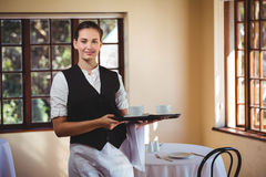 Portrait of smiling waitress holding a tray of coffee cups Royalty Free Stock Photo