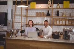 Portrait of smiling waitress and male owner using laptop at counter Stock Images