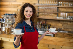 Portrait of smiling waitress offering cup of coffee Royalty Free Stock Images