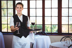 Portrait of smiling waitress offering a glass of red wine Stock Photos