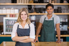 Portrait of smiling waitress standing with arms crossed. In cafe Royalty Free Stock Photography