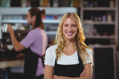 Portrait of smiling waitress standing with arms crossed. In cafe Royalty Free Stock Images