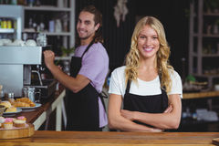 Portrait of smiling waitress standing with arms crossed at counter. In cafe Stock Photo