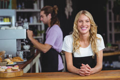 Portrait of smiling waitress standing at counter. In cafe Royalty Free Stock Photos