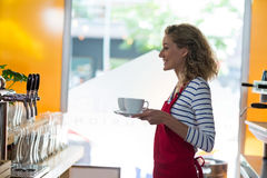 Portrait of smiling waitress standing with cup of coffee Stock Images