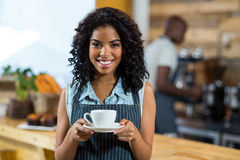 Portrait of smiling waitress standing with cup of coffee Stock Photography