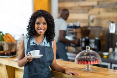 Portrait of smiling waitress standing with cup of coffee Royalty Free Stock Photos