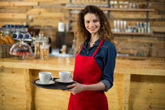 Portrait of smiling waitress standing with cup of coffee Royalty Free Stock Photo
