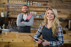 Portrait of smiling waitress standing with digital tablet Stock Photo