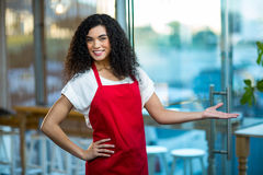 Portrait of smiling waitress standing with hand on hip Royalty Free Stock Photos