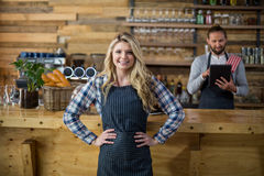 Portrait of smiling waitress standing with hands on hip at counter Stock Image