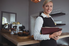 Portrait of smiling waitress standing with menu card Stock Image
