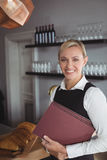 Portrait of smiling waitress standing with menu card Stock Photography