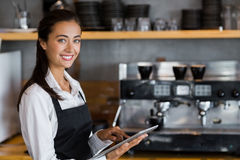 Portrait of smiling waitress using digital tablet. In cafe Royalty Free Stock Photography