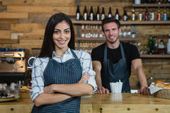 Portrait of smiling waitress and waiter standing at counter Stock Photo