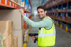 Portrait of smiling warehouse worker scanning box. In warehouse Stock Images